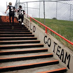 Monticello's Jared Anderson (5) and Zach Allred (14) run up stairs painted with the names of the team's seniors as they head to the field to face Layton Christian. Monticello dropped from 2A to 1A in 2001.