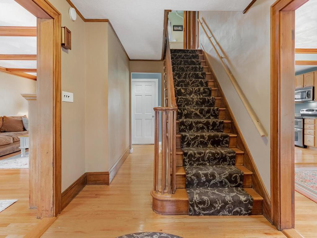 A set of stairs with carpeting off an entry foyer.