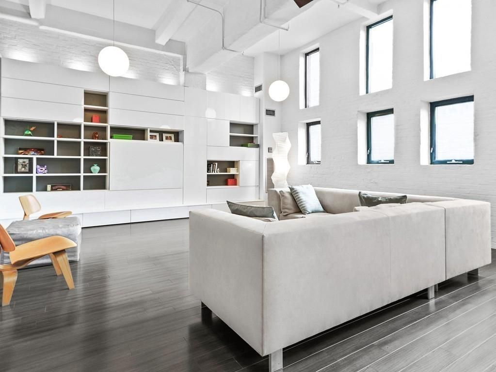 A capacious living room with a couch facing a bank of shelves.