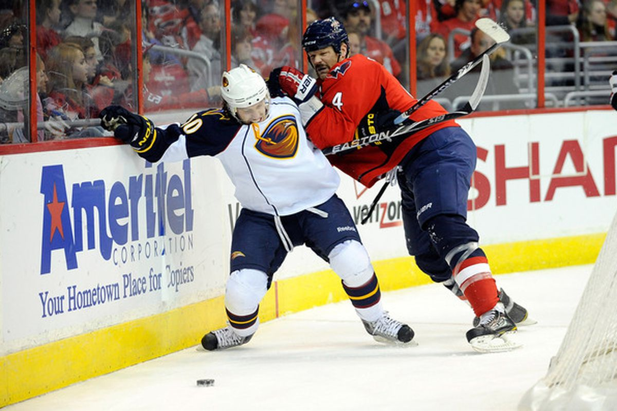 WASHINGTON - NOVEMBER 14:  Bryan Little #10 of the Atlanta Thrashers is checked by John Erskine #4 of the Washington Capitals at the Verizon Center on November 14 2010 in Washington DC.  (Photo by Greg Fiume/Getty Images)