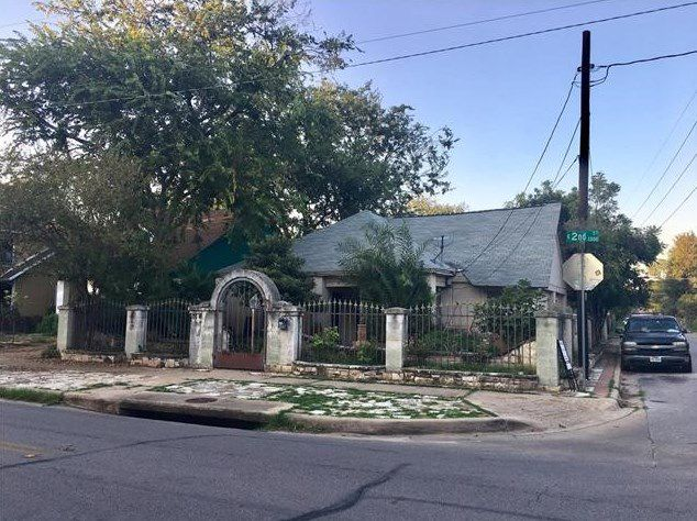 Old, small Spanish-style home with arched gate and iron fence