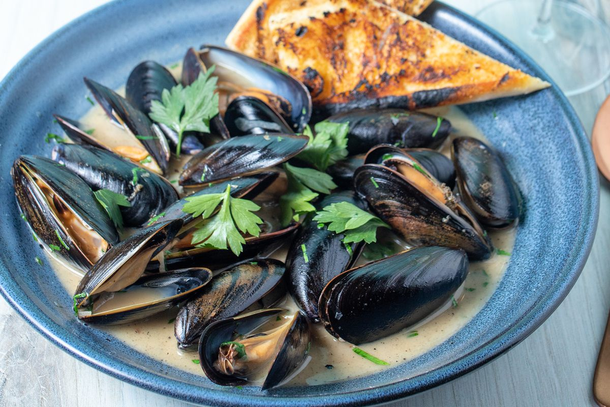 A blue plate with mussels in coconut milk