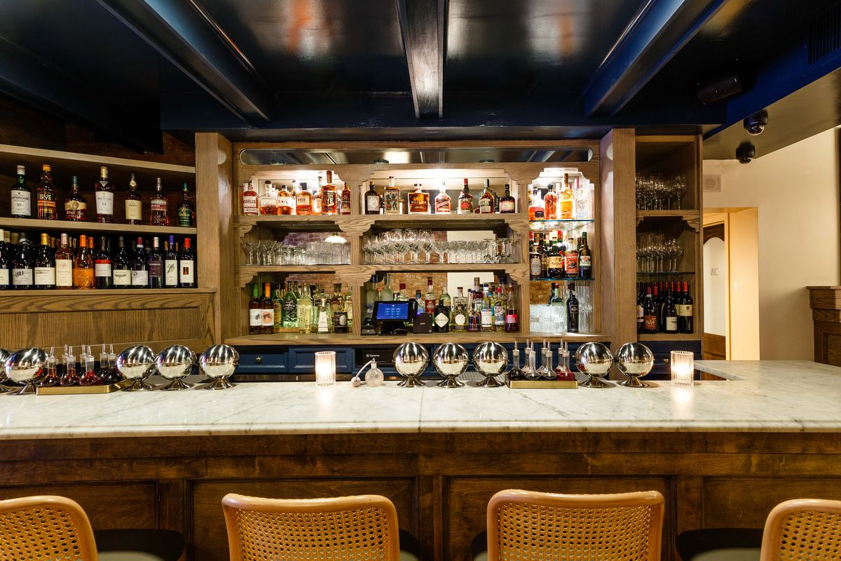 A marble counter in the front, straw-backed chairs against it, silver orbs on the marble counter, bar shelves with several liquor bottles on it behind it all.