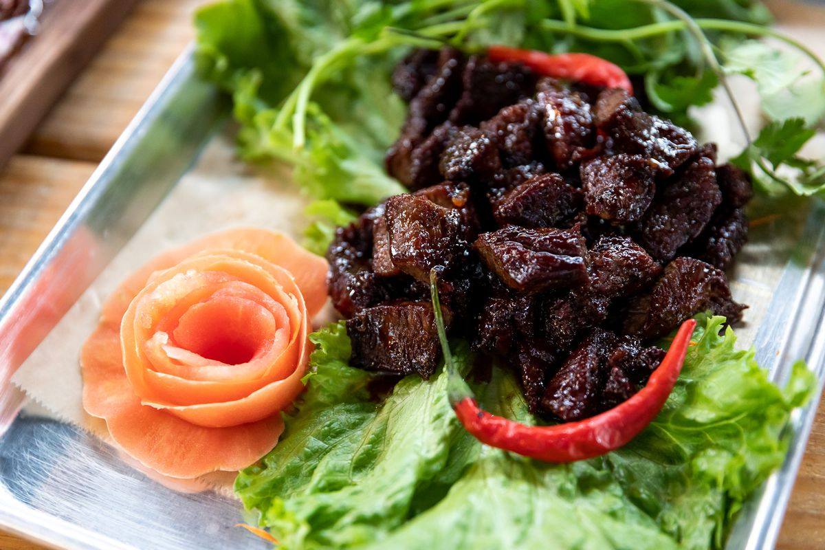 A pile of tiny pieces of candied beef on a tray with a bed of lettuce, two bright red chilis, and a rosette made from a radish.