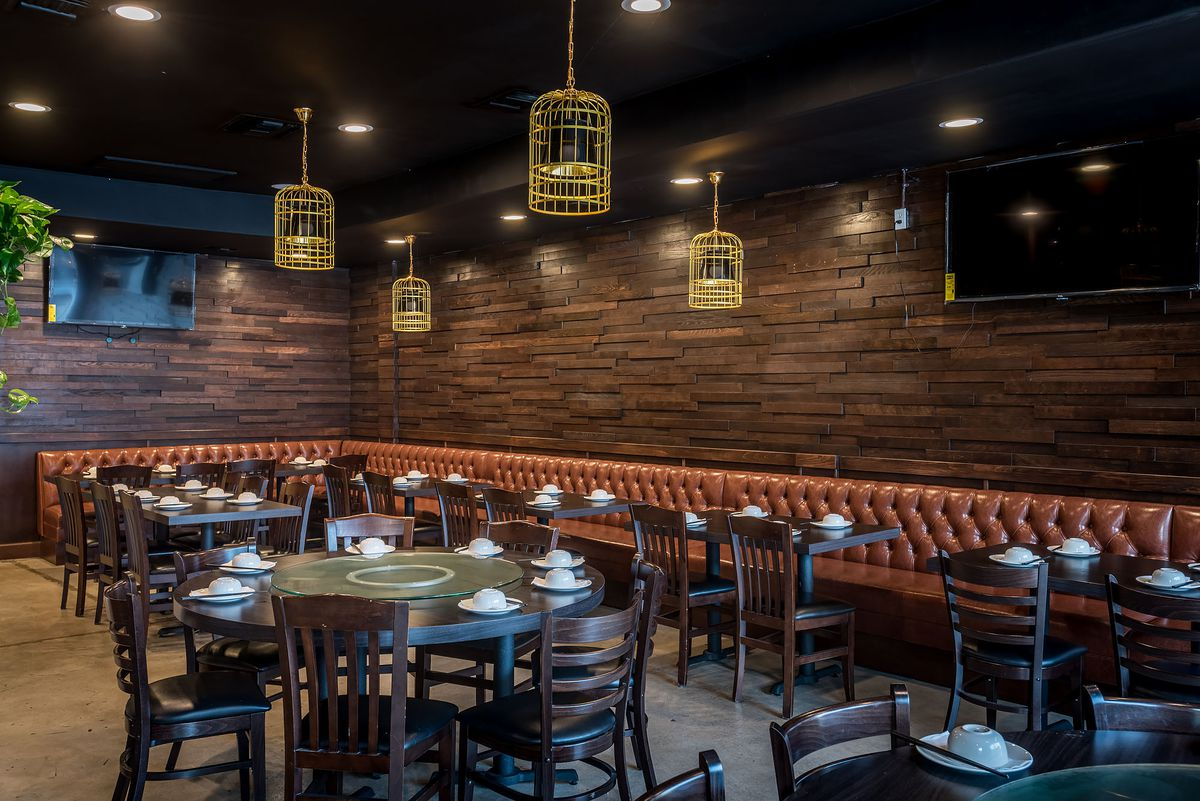 A long leather banquette and golden lighting inside a restaurant.