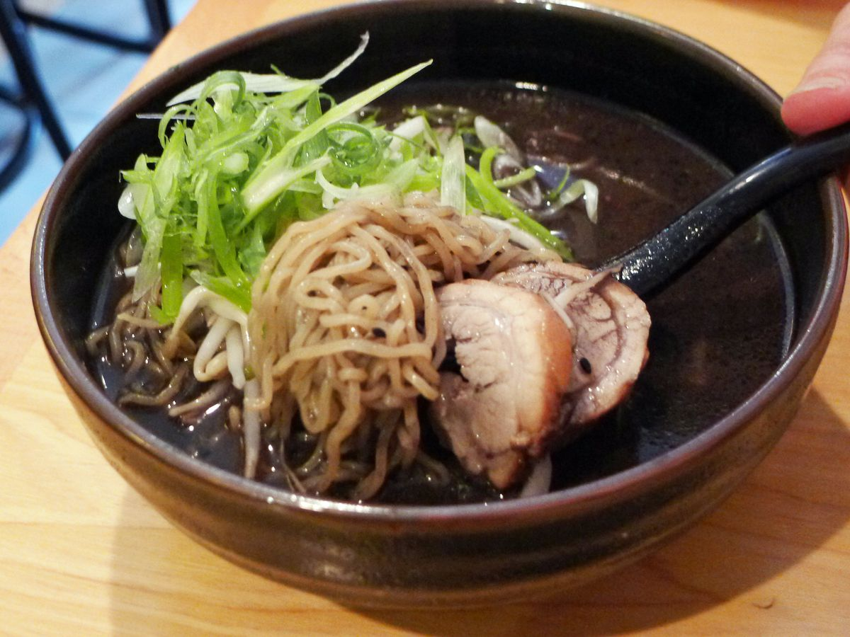 A black broth with ramen, chashu pork, and scallions in a black bowl