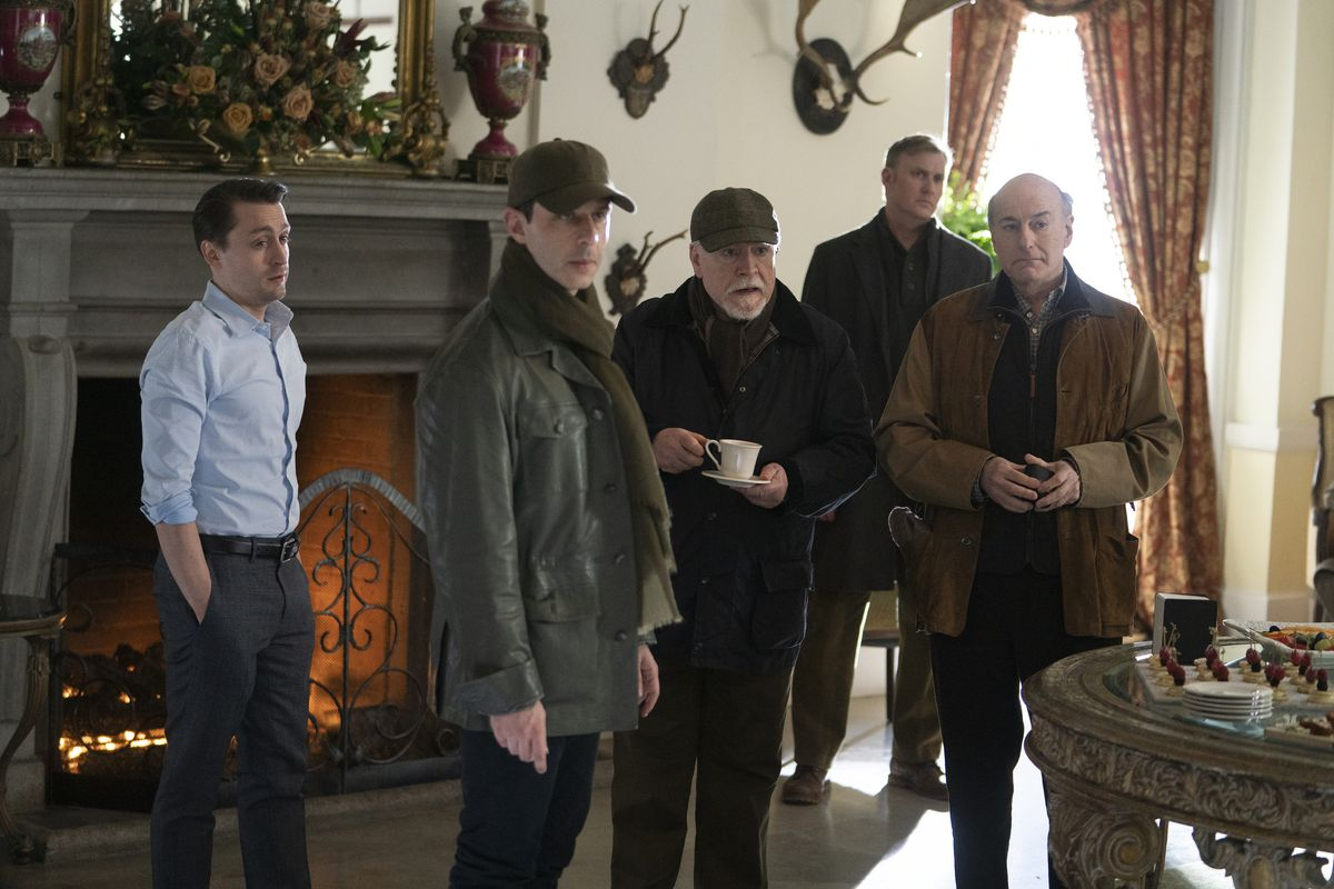 Roman (Kieran Culkin), Kendall (Strong), Logan (Brian Cox), a guard, and Frank (Peter Friedman) stand in front of a fireplace.