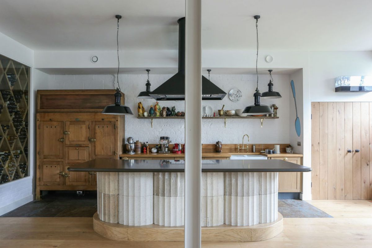 Interior shot of industrial looking kitchen with dark hood, dark counter on top of cast concrete columns, white brick walls, and natural oak cabinets.