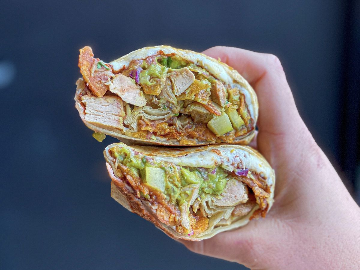 A cut chicken burrito showing its insides, held up next to a blue wall.