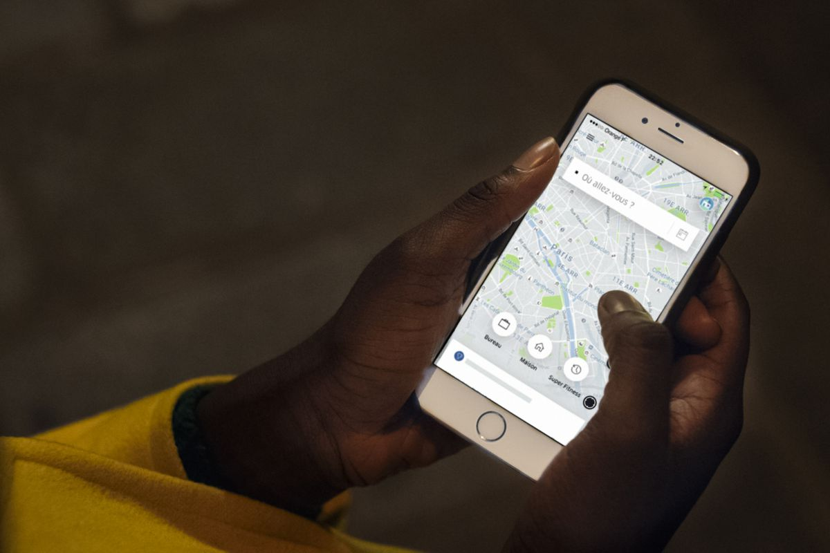 An iPhone in a black woman's hands, showing the Uber app