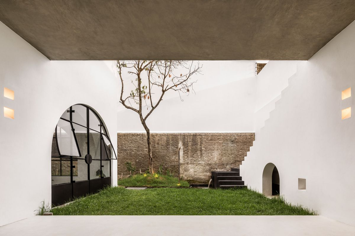 Courtyard with arched windows, grassy lawn, and concrete ceiling.