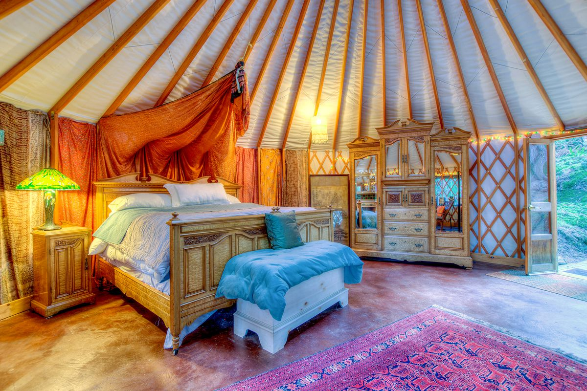 The interior of a yurt has a rug in the center of the room and a high, plush bed accented with a partial orange fabric canopy. A dresser sits in the background, and there's a bench covered in blue cloth at the foot of the bed.