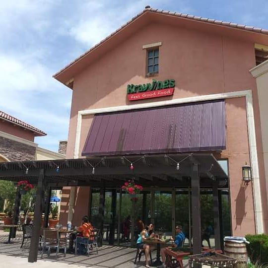 A patio in front of a restaurant with a peach exterior