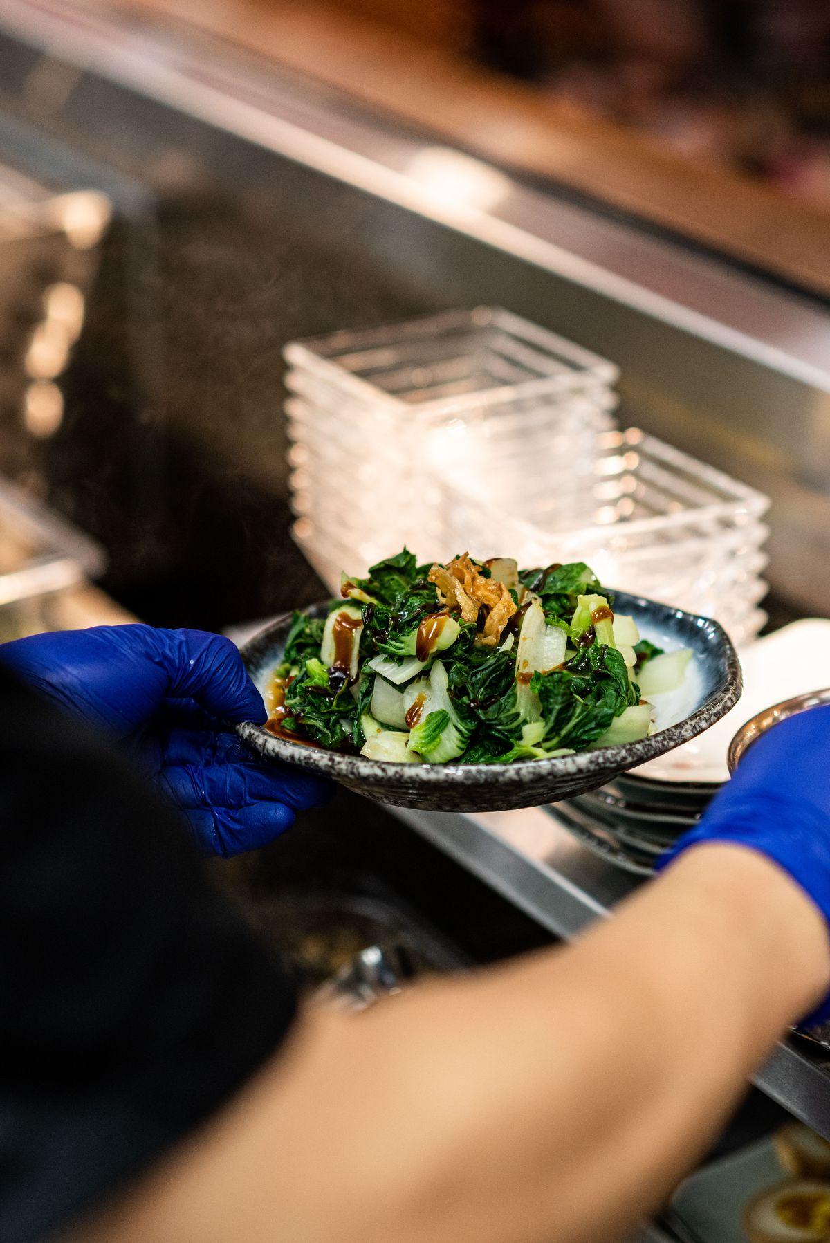 Braised greens being prepared in a kitchen.