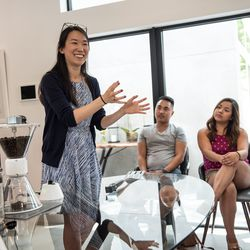 The Verge contributor Christine Sunu demos her silent coffee grinder for guests.