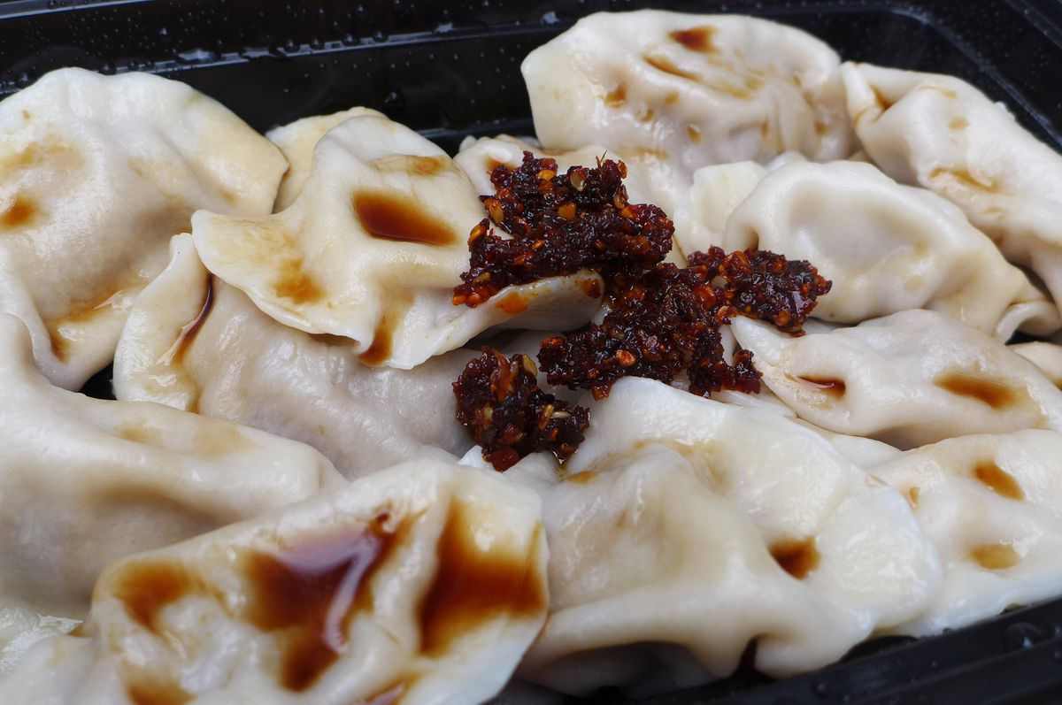 A container of oblong dumplings overlapping each other, with splotches of brown liquid and thick dark chili paste.