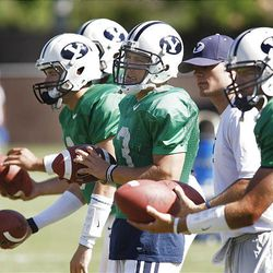 BYU quarterbacks, from left to right in green jerseys, Jason Munns, Jake Heaps, Riley Nelson and James Lark prepare to throw passes to receivers during drills at BYU's fall football camp.