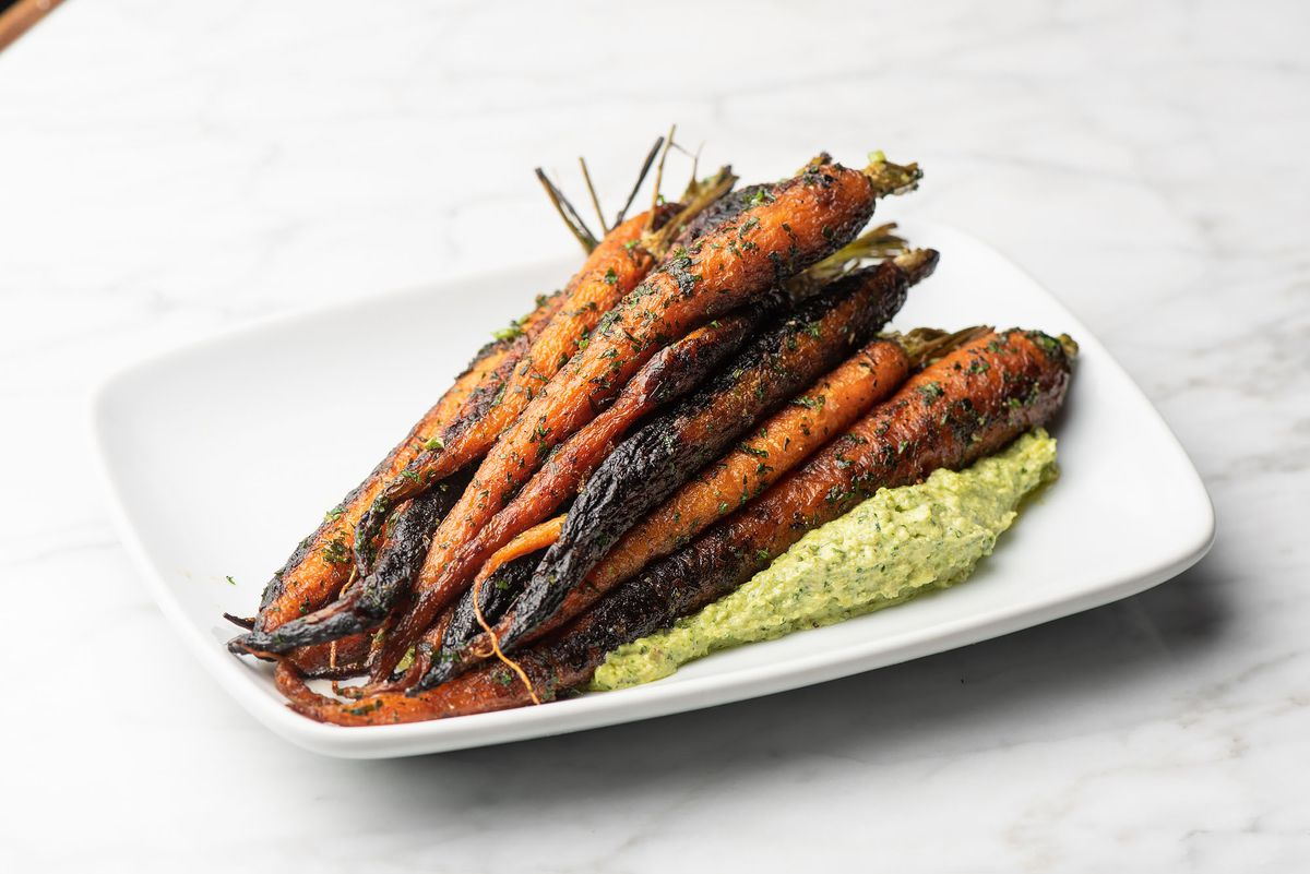 Long roasted carrots on a rectangular white plate.