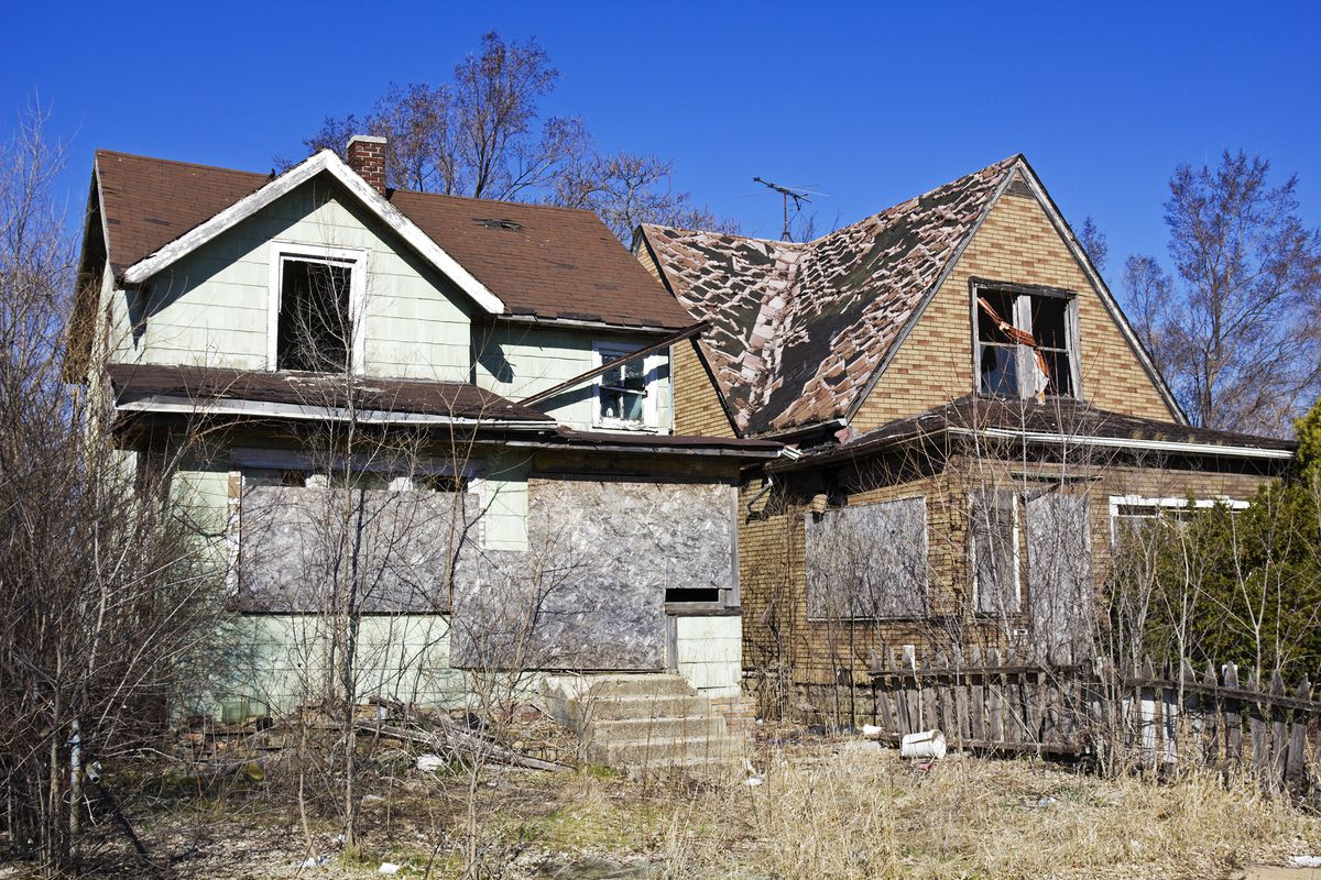 Two abandoned, boarded up homes on a street in Gary, Indiana.