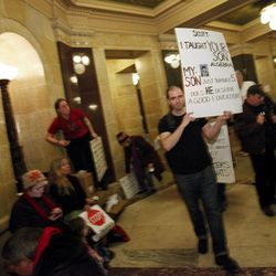 Teacher Michael Mulvey of West Allis, Wis., carries a sign in the rotunda at the State Capitol in Madison, Wis., Sunday, Feb. 20, 2011. Opponents to the governor's bill to eliminate collective bargaining rights for many state workers are on their sixth day of protesting.