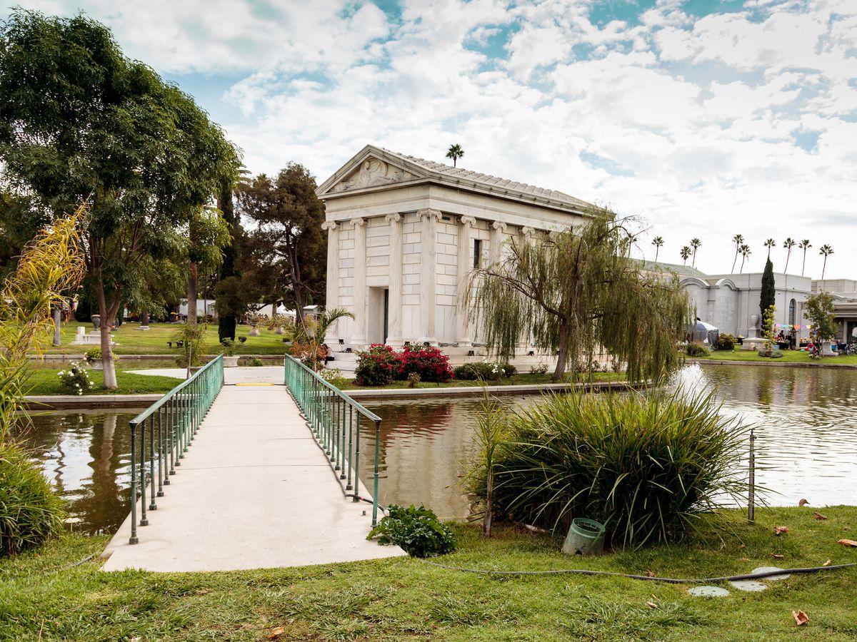 A bridge leading across a pond to a large mausoleum