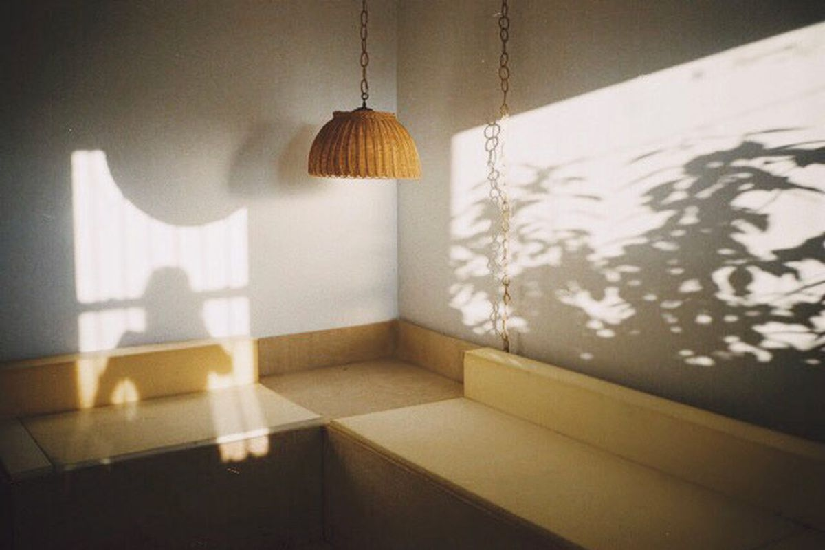 A shadowy corner of a room with a built-in yellow bench seating and yellow pendant lamp.