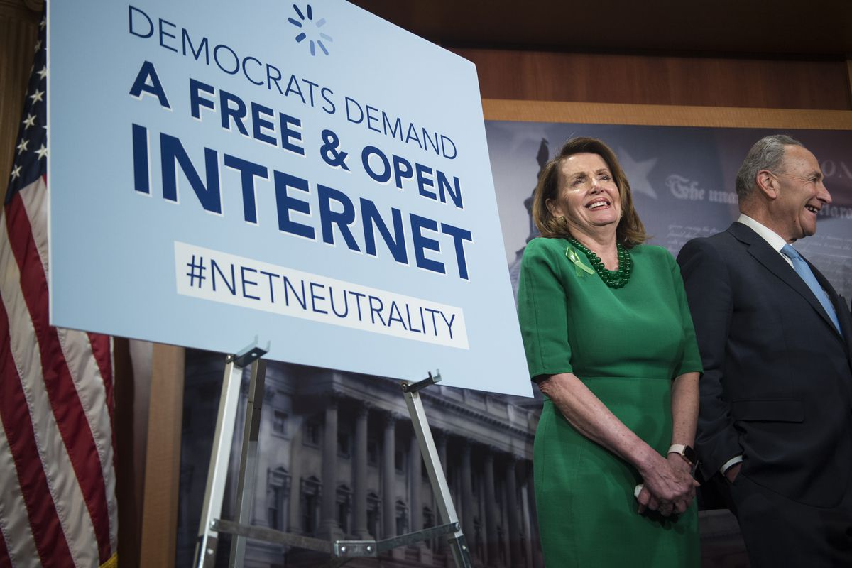 """Senate Minority Leader Sen. Charles Schumer, D-NY, and House Minority Leader Nancy Pelosi stand beside a sign that reads, """"Democrats demand a free and open internet #netneutrality."""""""