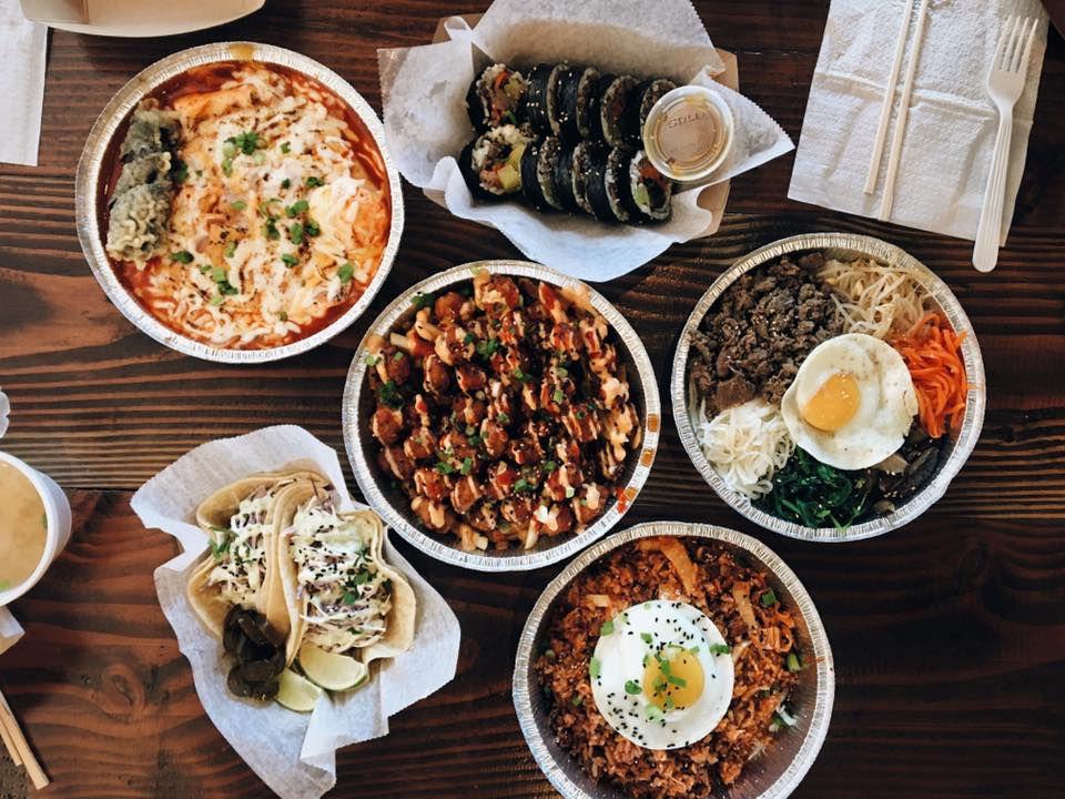 Overhead view of a table full of Korean food, including bibimbap and kimbap