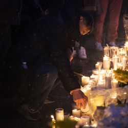 A man lights a candle as hundreds gather for a vigil in a parking lot in the 2000 block of South Wells in Chinatown, where Huayi Bian and Weizhong Xiong were shot to death, Wednesday, Feb. 12, 2020. Bian and Xiong were killed during an apparent robbery, for which Alvin Thomas faces two counts of first-degree murder.