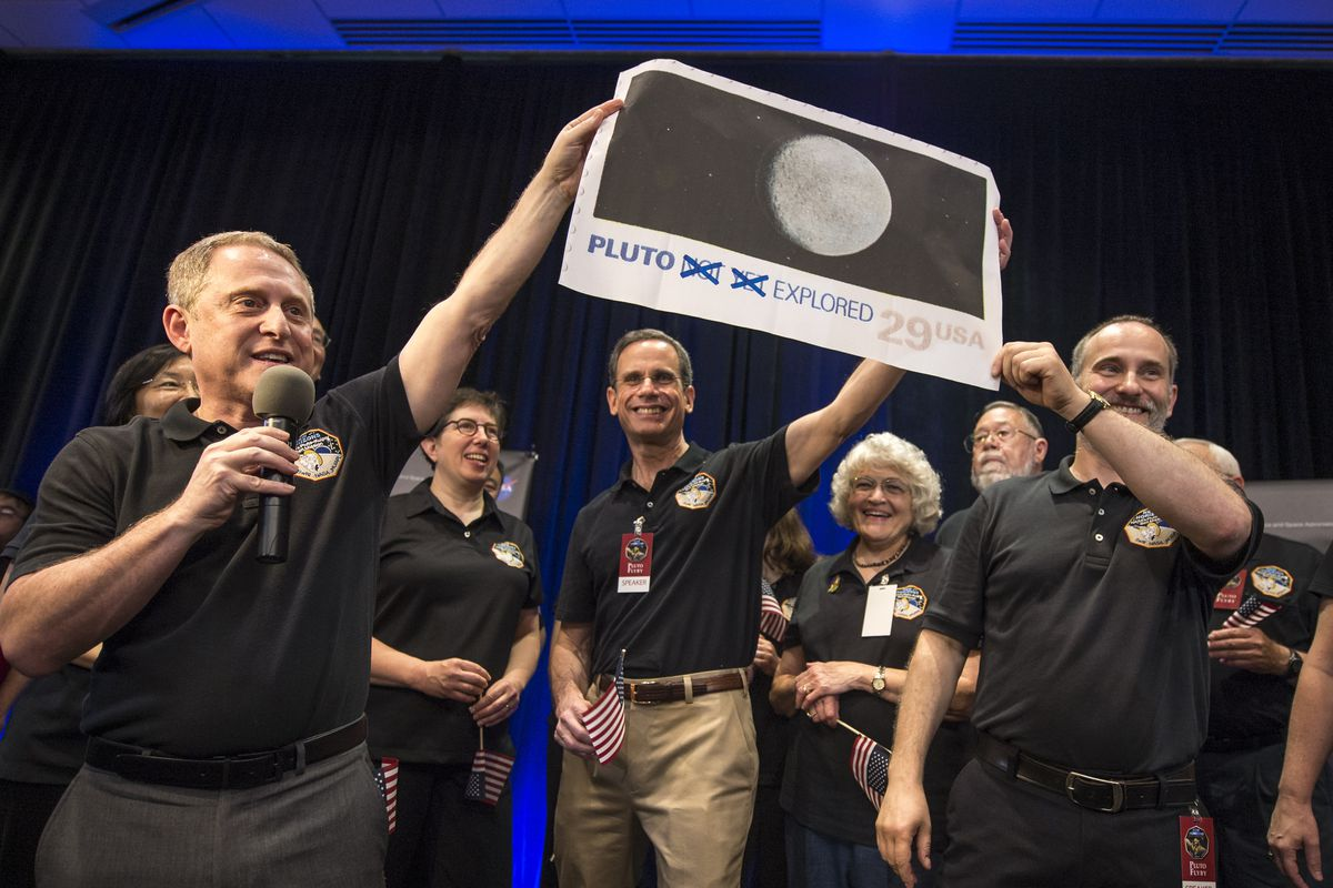 New Horizons mission scientists cheer the Pluto flyby.
