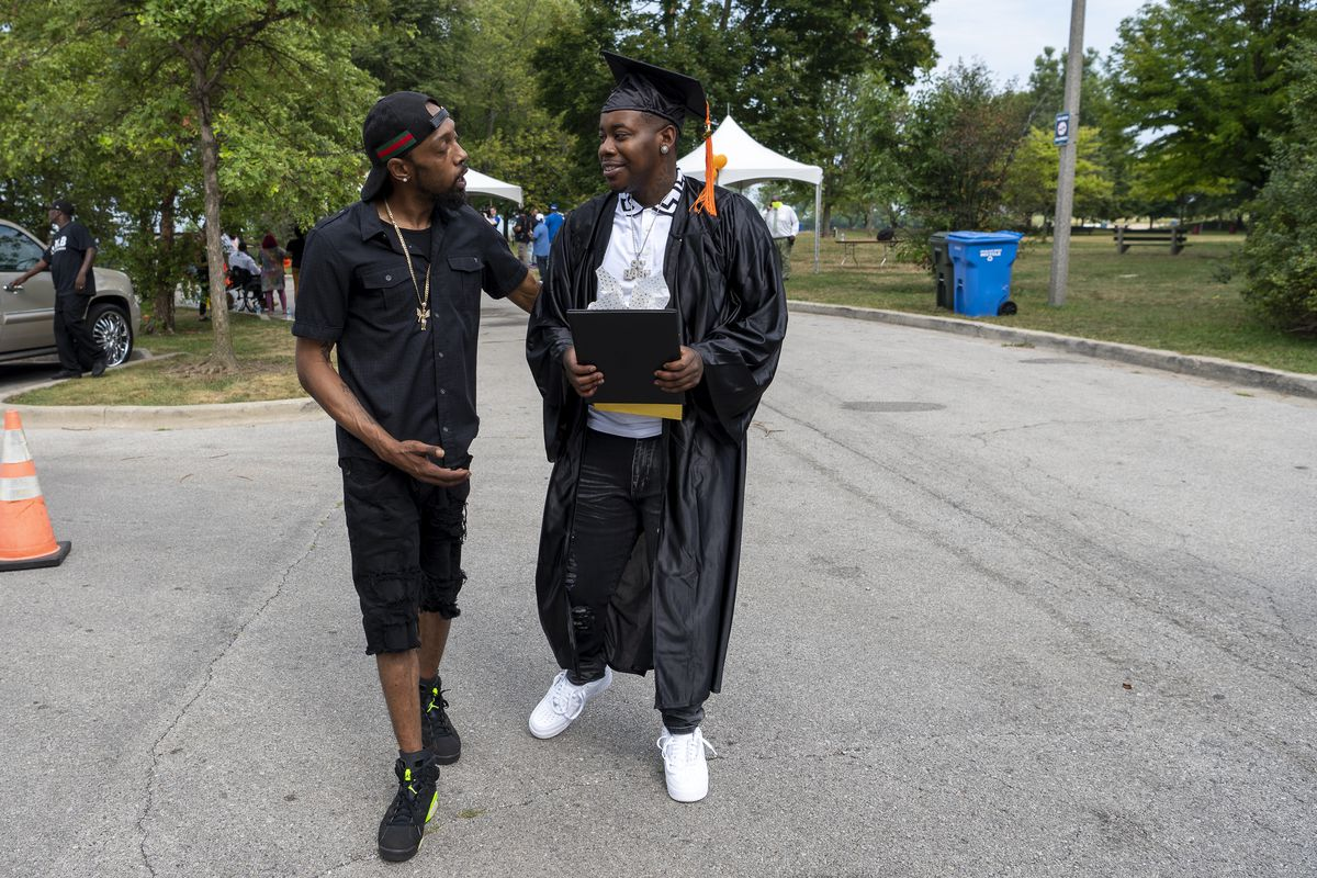 Terrance Henderson, Outreach Supervisor for Creating Real Economic Destiny, left, speaks to Lorenzo Taylor after he received his high school diploma during a graduation ceremony for graduates of the CRED program, at the South Shore Cultural Center, Thursday, Aug. 19, 2021.   Tyler LaRiviere/Sun-Times