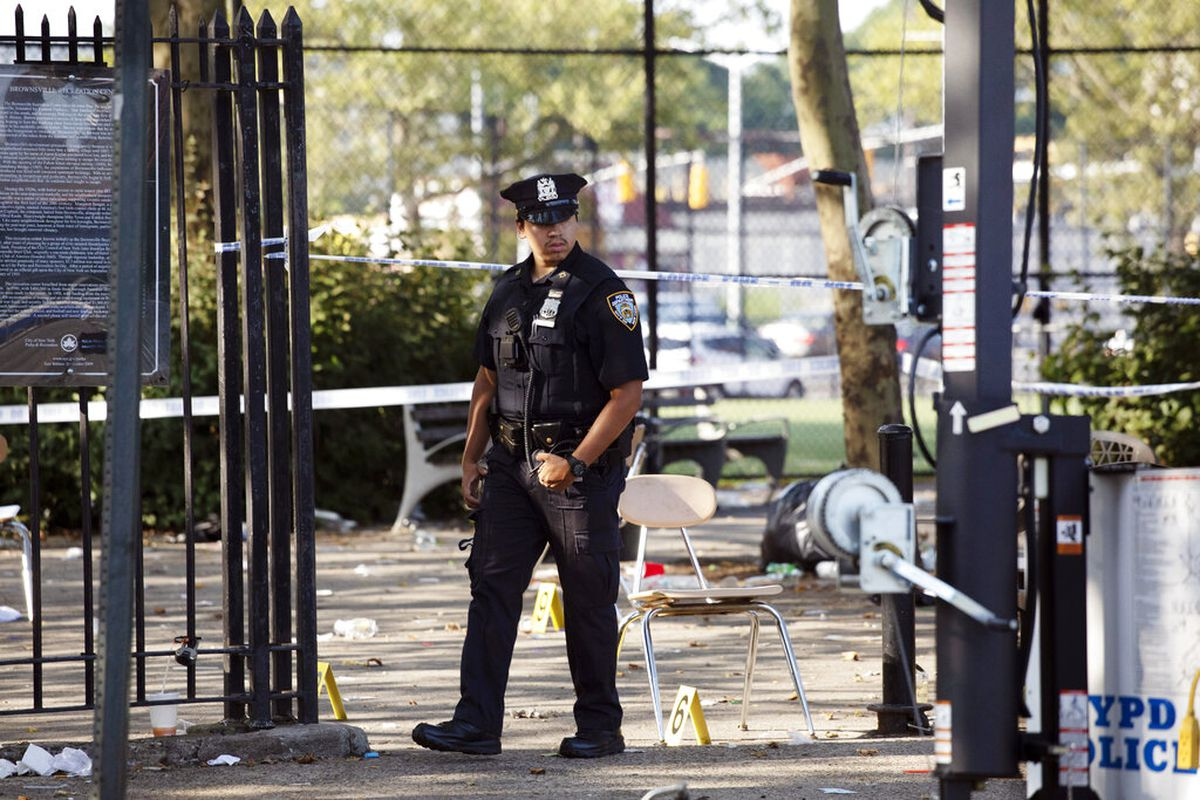 A police officer walks by yellow evidence markers at a playground in the Brownsville neighborhood in the Brooklyn borough of New York