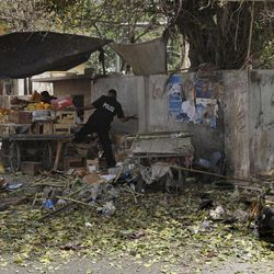 A Pakistani police officer searches the area after a suicide attack in Karachi, Pakistan on Thursday, April 5, 2012. Police say a suspected suicide bomber detonated explosives near a vehicle carrying a senior police official in the southern Pakistani city of Karachi, killing scores of people. (AP Photo)
