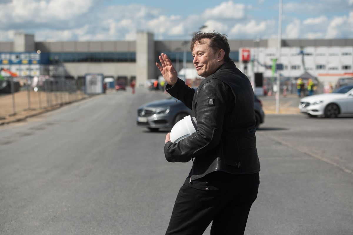 Tesla boss Elon Musk waves from the parking lot while visiting a factory construction site in Grünheide, Germany.