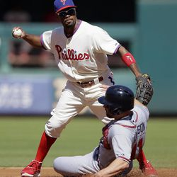 Philadelphia Phillies shortstop Jimmy Rollins, top, forces out Atlanta Braves' Reed Johnson out at second base on a fielder's choice by Jason Heyward in the first inning of a baseball game, Sunday, Sept. 23, 2012, in Philadelphia. Heyward was safe at first base.