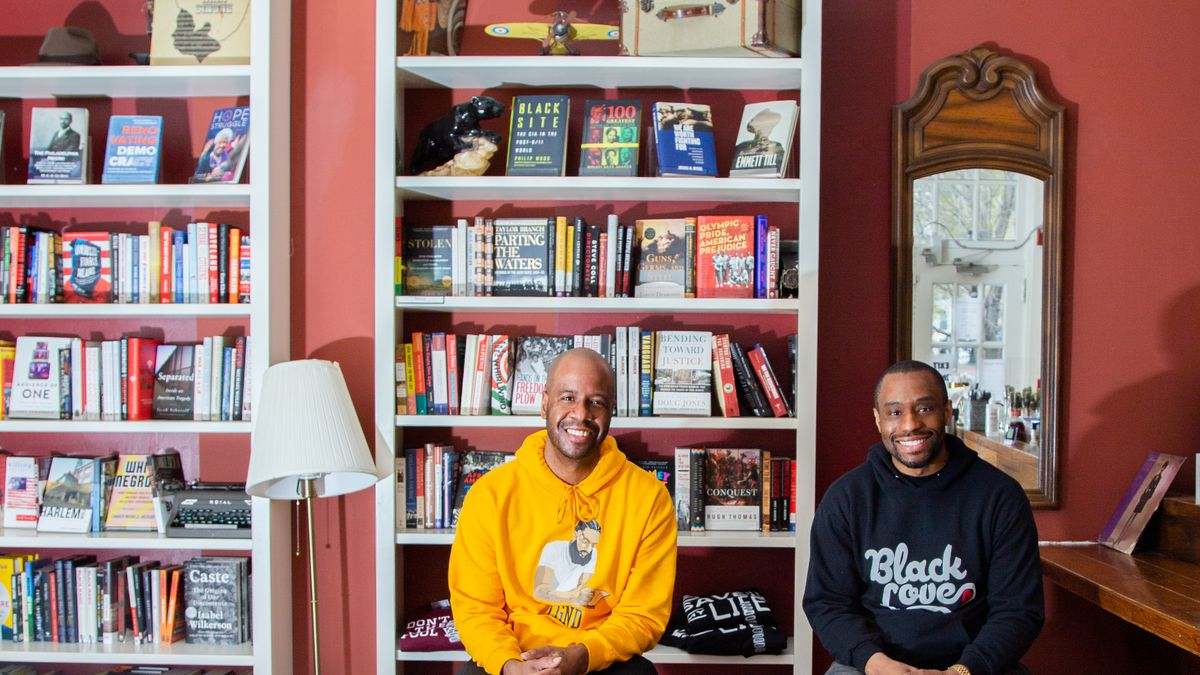 Justin Moore and Marc Lamont Hill sit in front of a bookshelf and lamp at Uncle Bobbie's Coffee and Books in Germantown