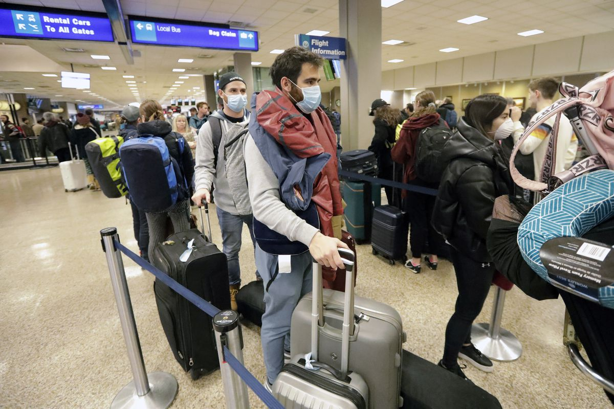 Masked travelers stand in line with luggage before getting to the ticket counter at the Salt Lake City International Airport Sunday, March 15, 2020, in Salt Lake City.