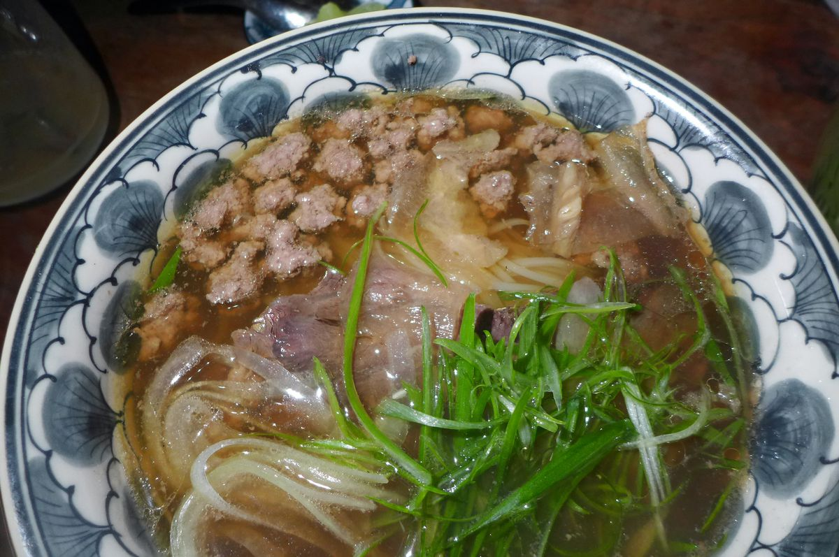 A jam packed bowl of dark broth, noodles, tiny meatballs, and green herbs.