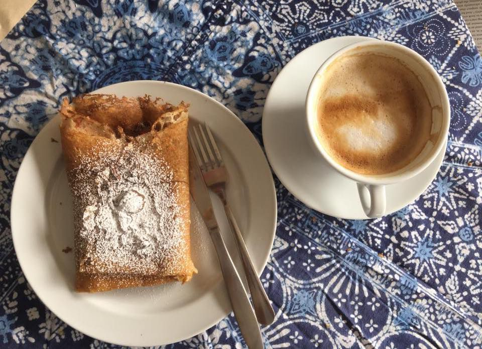 Crêpe with powdered sugar and a cappuccino