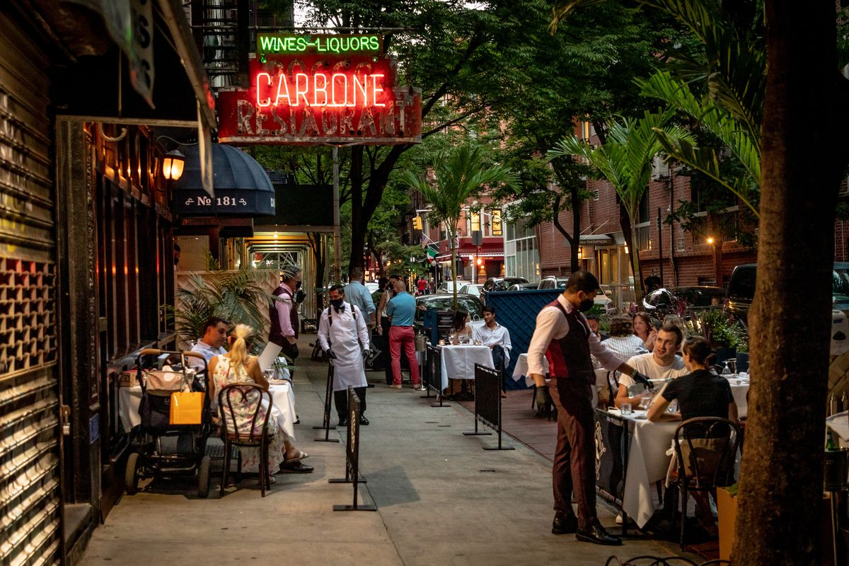 """Waiters attend to groups of diners sitting at outdoor tables on a tree-lined street. To the left, a neon illuminated sign """"Wines Liquors Carbone"""" shines."""