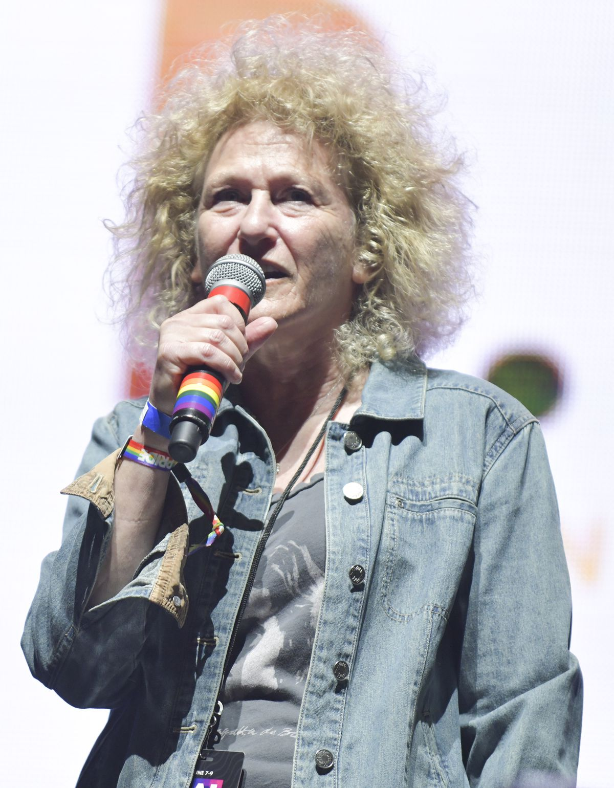 West Hollywood City Council member and now mayor Lauren Meister holding rainbow microphone wearing a jean jacket speaking at Pride 2019.