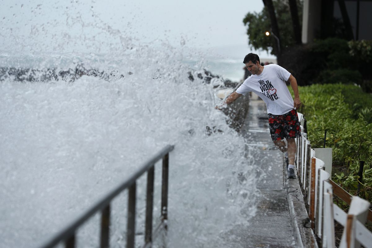 A man avoids getting splashed by a large wave on a walkway along a beach ahead of Hurricane Lane, Thursday, Aug. 23, 2018, in Honolulu.