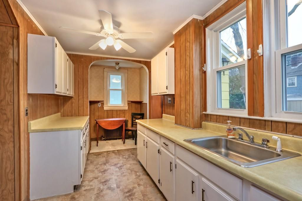 An older kitchen with two counters, and it ends in a seating area.