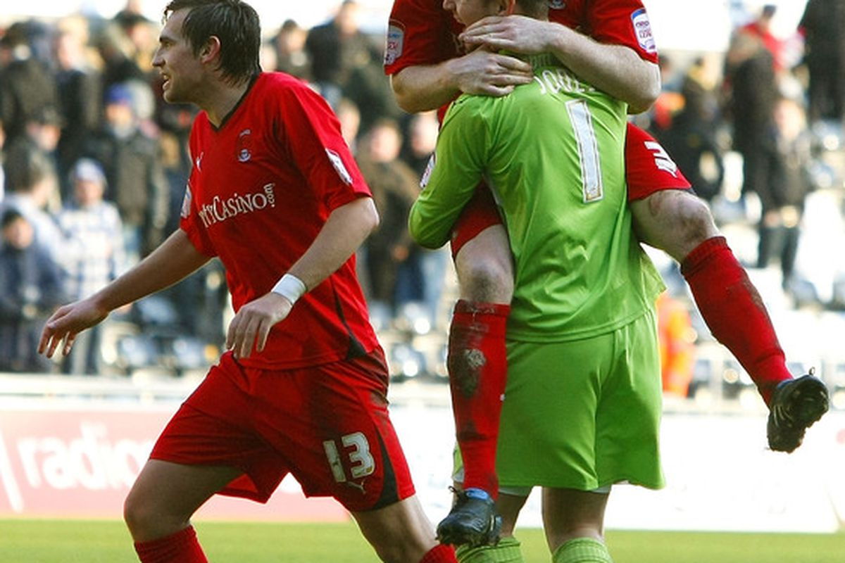 Happier times - Leyton Orient players Charlie Daniels, Jamie Jones and Andrew Whing (from L to R) celebrate beating Swansea City in an FA Cup 4th Round match in 2011. (Photo by Tom Dulat/Getty Images)