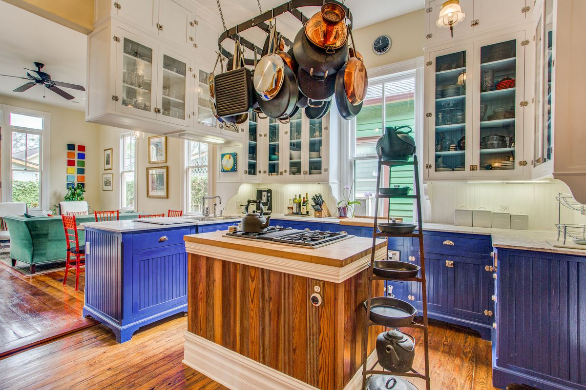 A kitchen has blue cabinetry in the lower cabinets and white in the upper cabinets. Pots hang over a wood kitchen island in the center.