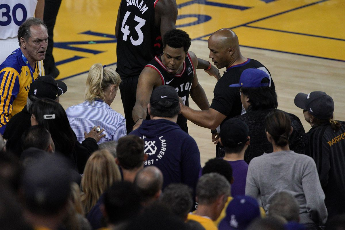 Toronto Raptors guard Kyle Lowry, middle, gestures next to referee Marc Davis (8) near the front row of fans during the second half of Game 3 of basketball's NBA Finals between the Golden State Warriors and the Raptors in Oakland, Calif., Wednesday, June