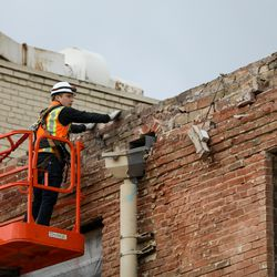 A worker checks the brick facade of a building at 500 South and 400 West in Salt Lake City after a 5.7 magnitude earthquake centered in Magna hit early on Wednesday, March 18, 2020.