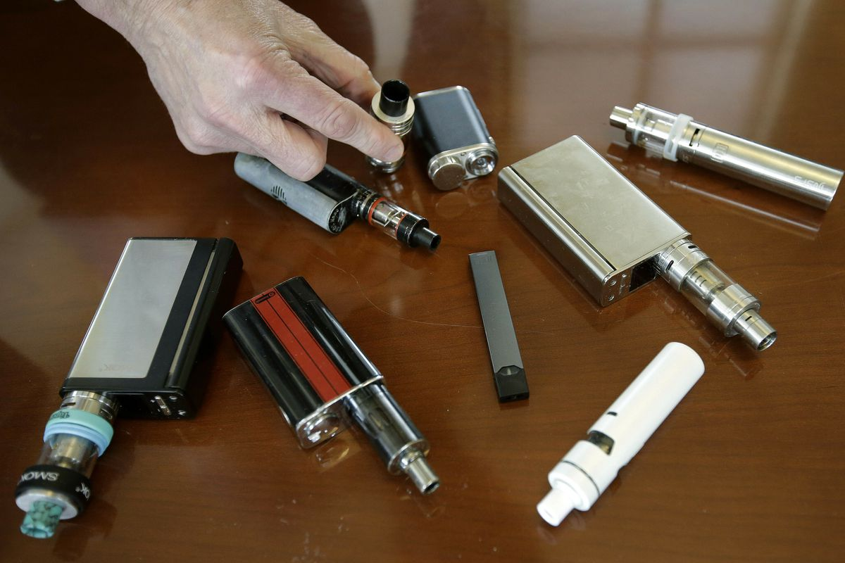In this April 10, 2018, file photo, a high school principal displays vaping devices that were confiscated from students in such places as restrooms or hallways at the school in Massachusetts. U.S. health officials are scrambling to keep e-cigarettes away