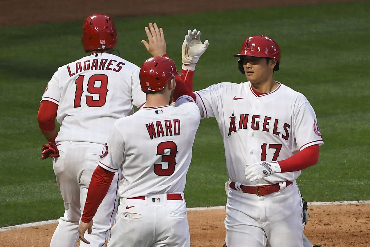 Los Angeles Angels designated hitter Shohei Ohtani is congratulated by right fielder Taylor Ward and left fielder Juan Lagares after hitting a two-run home run against the Cleveland Indians during the second inning at Angel Stadium.