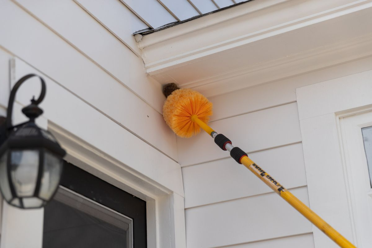 A yellow pest-control duster reaches to a corner on the exterior of a white home to remove an insect nest.